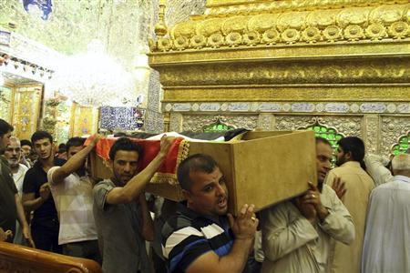 Mourners carry the coffin of a victim killed during an attack on a prison in Taji, during a funeral at the Imam Ali shrine in Najaf, 160 km (100 miles) south of Baghdad July 22, 2013. REUTERS/Haider Ala