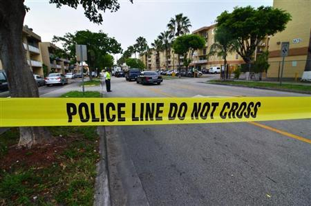 Police tape blocks the street to an apartment building after a shooting incident which began Friday evening left seven people dead in Hialeah, Florida, July 27, 2013. REUTERS/Gaston De Cardenas