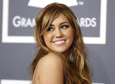 Miley Cyrus poses on arrival at the 53rd annual Grammy Awards in Los Angeles, California February 13, 2011. REUTERS/Danny Moloshok