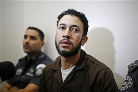 Palestinian Wael Abu Rida (C) sits next to Israeli prison guards before his indictment at the district court in the southern Israeli city of Beersheba July 19, 2013. REUTERS/Amir Cohen