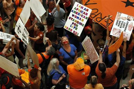 Abortion rights (in orange) and anti-abortion advocates (in blue) rally in the rotunda of the State Capitol, as the state Senate meets to consider legislation restricting abortion rights in Austin, Texas July 12, 2013. REUTERS/Mike Stone
