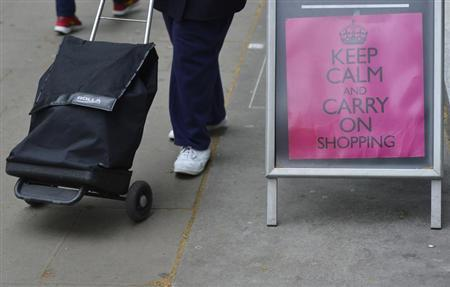 Shoppers walk pass a retail sign that reads ''Keep Calm and Carry on Shopping'', in central London May 10, 2013. REUTERS/Toby Melville
