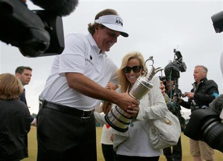 Phil Mickelson of the U.S. (L) holds the Claret Jug as he celebrates with his wife Amy after winning the British Open golf championship at Muirfield in Scotland July 21, 2013. REUTERS/Brian Snyder