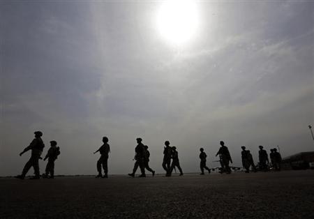 Nigerian soldiers walk on the tarmac of the Bamako airport January 22, 2013. REUTERS/Eric Gaillard