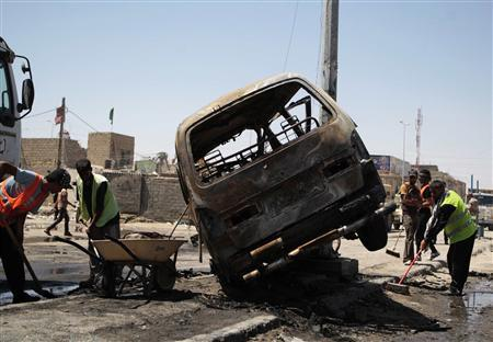 Street cleaners remove debris on the road at the site of a car bomb attack in Basra, 420 km (260 miles) southeast of Baghdad, July 29, 2013. REUTERS/Stringer