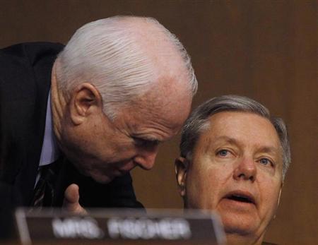 Senators John McCain (R-AZ) (L) and Lindsey Graham (R-SC) (R) confer at the Senate Armed Services Committee in Washington March 5, 2013. REUTERS/Gary Cameron