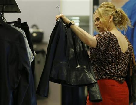 A shopper looks at a leather jacket from the new autumn/winter women's wear collection in Marks & Spencer's in central London on July 25, 2013. REUTERS/Olivia Harris