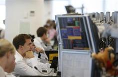 Брокеры в торговом зале инвесткомпании Ренессанс Капитал в Москве 15 сентября 2009 года. Российские фондовые индексы незначительно снижаются в начале торгов среды, а бумаги производителей удобрений, которые накануне подверглись распродажам, пытаются восстановиться. REUTERS/Denis Sinyakov