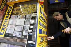 Работник пункта обмена валют в Будапеште обновляет курсы 30 января 2009 года. Доллар незначительно вырос к корзине мировых валют, поскольку инвесторы проявляют осторожность в ожидании заявления ФРС по итогам совещания. REUTERS/Laszlo Balogh