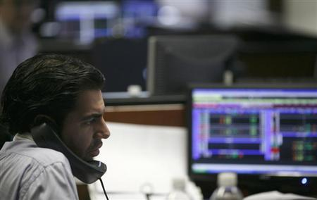 A broker talks on the phone as he monitors stock prices at Multiva Bank in Mexico City August 9, 2011. REUTERS/Carlos Jasso