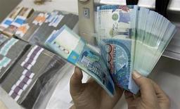 Сотрудник отделения Казкоммербанка в Алма-Ате считает тенге 4 февраля 2010 года. Второй по величине активов в Казахстане банк, Казкоммерц, увеличил консолидированную чистую прибыль до 15,334 миллиарда тенге ($100 миллионов) в первой половине 2013 года с 12,988 миллиарда за аналогичный период прошлого года. REUTERS/Shamil Zhumatov