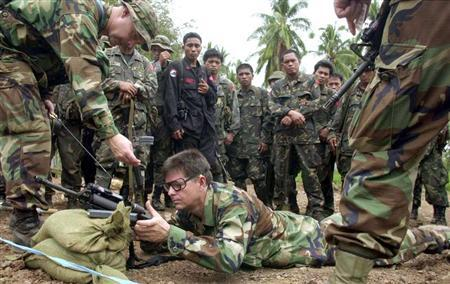 American special forces soldiers show Filipino army troopers techniques in firing their rifles during marksmanship training at a firing range on Basilan Island in the southern Philippines April 11, 2002. RTXL76Z