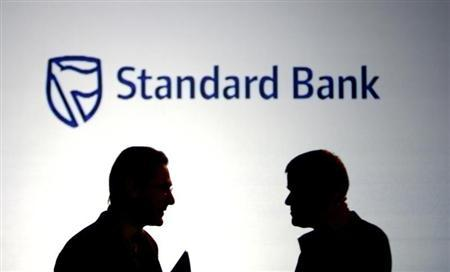 Businessmen chat in front of a Standard Bank logo in Sandton outside Johannesburg in this October 25, 2007 file photo. REUTERS/Siphiwe Sibeko