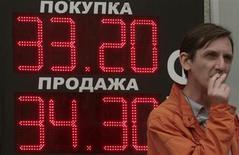 Человек курит на фоне вывески пункта обмена валюты в Москве 1 июня 2012 года. Рубль подешевел к бивалютной корзине до минимальных с сентября 2009 года значений из-за нежелания рисковать перед важными событиями недели и за счет спроса на валюту, формируемого оттоком капитала, конвертацией в валюту дивидендных выплат, а также ростом импорта услуг в конце лета. REUTERS/Sergei Karpukhin