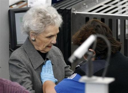 A Transportation Security Administration (TSA) worker (R) rubs her hands across a elderly female traveler's chest during a patdown search at Denver International Airport in Denver November 23, 2010. REUTERS/Rick Wilking