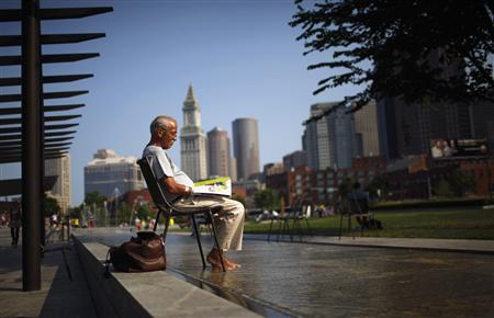 A man soaks his feet in a fountain while reading a magazine on the Rose Kennedy Greenway on a warm summer afternoon in Boston, Massachusetts July 19, 2011. REUTERS/Brian Snyder