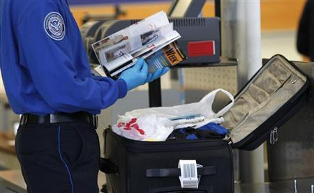 A Transportation Security Administration (TSA) officer inspects items from a piece of luggage at Los Angeles International Airport in Los Angeles, California March 4, 2013. REUTERS/Mario Anzuoni
