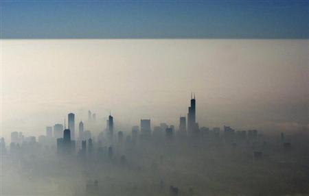 Blue sky is seen over a blanket of fog enveloping the skyline of Chicago, as photographed from an airplane window November 21, 2012. REUTERS/Kevin Lamarque