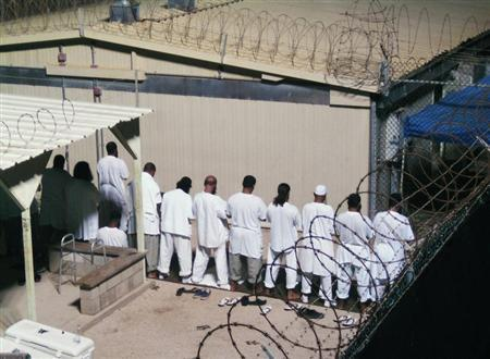 Detainees participate in an early morning prayer session at Camp IV at the detention facility in Guantanamo Bay U.S. Naval Base August 5, 2009. REUTERS/Deborah Gembara