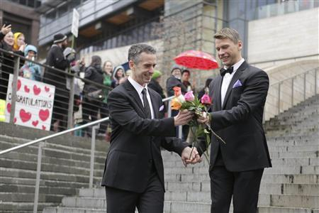 Seattle gay-rights advocate and journalist Dan Savage (L) and Terry Miller sort through roses on the steps of City Hall after getting married at Seattle City Hall in Seattle, Washington, in this December 9, 2012 file photo. REUTERS/Cliff Despeaux/Files