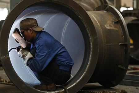 An employee welds a water turbine at a factory in Jinhua, Zhejiang province May 23, 2013. REUTERS/William Hong
