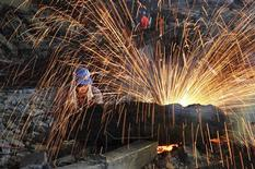 A labourer cuts scrap steel at a factory of Dongbei Special Steel Group Co., Ltd., in Dalian, Liaoning province July 24, 2013. REUTERS/China Daily
