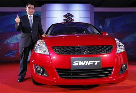 Suzuki Motor Corp's Toshihiro Suzuki poses with a new Suzuki Swift during a news conference in Bangkok March 21, 2012. REUTERS/Chaiwat Subprasom