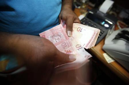 A money changer counts Malaysia's ringgit notes in Kuala Lumpur January 29, 2013. REUTERS/Bazuki Muhammad