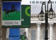 Вывески банков Lloyds и Co-Operative в Бирмингеме 24 апреля 2013 года. Получивший государственную поддержку британский банк Lloyds рассчитывает выполнить план сокращения расходов и достижения ориентиров капитала и маржи ранее, чем ожидалось, заложив основу для восстановления дивидендных выплат и позволив властям начать продажу акций из государственной доли. REUTERS/Darren Staples