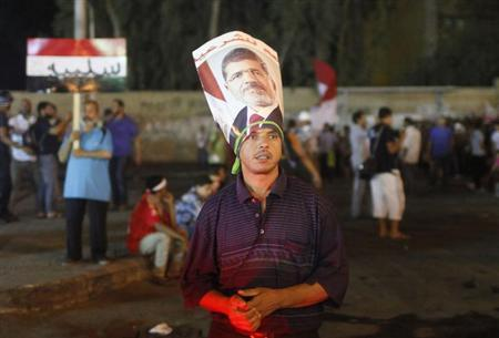 A supporter of deposed Egyptian president Mohamed Mursi, wearing a Mursi poster around his head, stands with other protesters during an anti-army rally that started from their sit-in area around Raba' al-Adawya mosque, in Nasr City area, east of Cairo, July 30, 2013.REUTERS/Asmaa Waguih