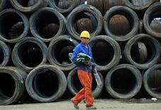 A labourer walks past piles of steel coils at a steel wholesale market in Shenyang, Liaoning province July 15, 2013. REUTERS/Stringer