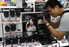A customer tries a Sony Corp Alpha a99 digital camera at an electronic store in Tokyo August 1, 2013. Sony Corp reported a higher than expected first-quarter operating profit on Thursday, boosted by strong sales of its flagship Xperia smartphones in Japan and rising shipments of image sensors to phone makers. REUTERS/Issei Kato