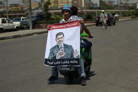 A supporter of deposed Egyptian President Mohamed Mursi holds a poster of him as he rides on a scooter during a march from the Al-Fath Mosque to the defence ministry, in Cairo July 30, 2013. REUTERS/Mohamed Abd El Ghany