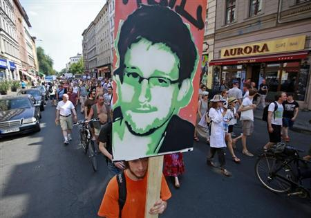 A protester carry a portrait of Edward Snowden during a demonstration against secret monitoring programmes PRISM, TEMPORA, INDECT and showing solidarity with whistleblowers Edward Snowden, Bradley Manning and others in Berlin July 27, 2013. REUTERS/Pawel Kopczynski