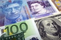 """Банкноты доллара США, евро, британского фунта и швейцарского франка в Варшаве 26 января 2011 года. Золотовалютные резервы РФ выросли на $3,7 миллиарда за прошлую неделю благодаря положительной переоценке золота, евро и британского фунта, а также за счет операций """"валютный своп"""" коммерческих банков с ЦБ. REUTERS/Kacper Pempel"""
