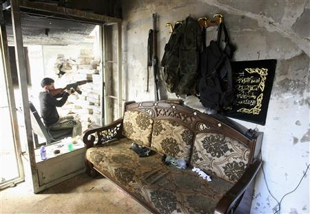 A Free Syrian Army fighter takes aim as he sits on a chair in Aleppo's Salaheddine neighbourhood July 30, 2013. Picture taken July 30, 2013. REUTERS/ Ammar Abdullah