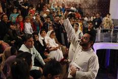 """Apresentador Aamir Liaquat Hussain, do canal Geo TV, durante a transmissão ao vivo de seu programa """"Amaan Ramazan"""", Karachi, no Paquistão. Hussain, um homem de 41 anos, distribui bebês ao vivo, no que muitos consideram ser o mais polêmico conteúdo já feito na guerra por audiência na televisão. 26/07/2013. REUTERS/Akhtar Soomro"""