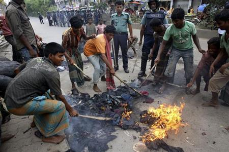 Locals try to extinguish a fire as members of police patrol, after Bangladesh Jamaat-e-Islami activists set fire to a cotton store near Kamalapur railway station in Dhaka August 1, 2013. REUTERS/Andrew Biraj