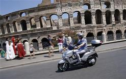 Matteo Achilli rides a scooter past the Colosseum in Rome July 25, 2013. REUTERS/Tony Gentile