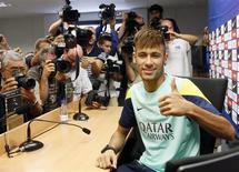 Atacante Neymar cercado pelos jornalistas antes de sua primeira coletiva de imprensa após um treino do Barcelona, no centro de treinamento do time próximo a Barcelona. Neymar afirmou que está realizando um sonho de infância ao treinar ao lado dos astros do time catalão, como Lionel Messi. 1/08/2013. REUTERS/Gustau Nacarino