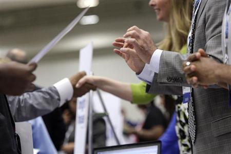 Corporate recruiters (R) gesture and shake hands as they talk with job seekers at a Hire Our Heroes job fair targeting unemployed military veterans and sponsored by the Cable Show, a cable television industry trade show in Washington, June 11, 2013. REUTERS/Jonathan Ernst