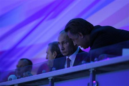 Russian President Vladimir Putin (L) listens to Sports Minister Vitaly Mutko as he watches the ceremony during the opening of the Summer Universiade at the Kazan Arena Stadium in Kazan, July 6, 2013. REUTERS/Mikhail Klimentyev/RIA Novosti/Kremlin