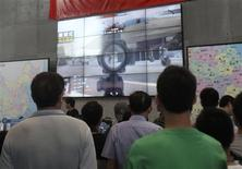 """Visitors look at a screen, displaying the video game """"Glorious Mission Online"""", under a Chinese national flag during the China Digital Entertainment Expo and Conference (ChinaJoy) in Shanghai July 25, 2013. REUTERS/Stringer"""
