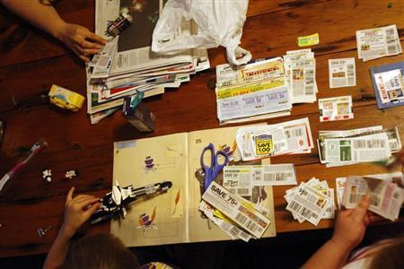 Katie Busker, 30, clips coupons as her son, Austin Spiker, 6, plays with Legos at the dinner table in Independence, Iowa July 5, 2011. REUTERS/Jessica Rinaldi
