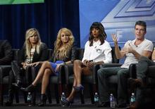 "Judge Simon Cowell speaks next to fellow judges (from L-R) Demi Lovato, Paulina Rubio and Kelly Rowland at a panel for the television series ""The X Factor"" during the Fox portion of the Television Critics Association Summer press tour in Beverly Hills, California August 1, 2013. REUTERS/Mario Anzuoni"