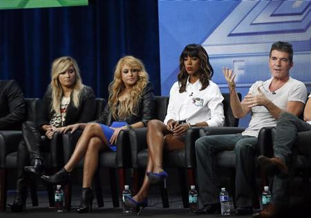 Judge Simon Cowell speaks next to fellow judges (from L-R) Demi Lovato, Paulina Rubio and Kelly Rowland at a panel for the television series ''The X Factor'' during the Fox portion of the Television Critics Association Summer press tour in Beverly Hills, California August 1, 2013. REUTERS/Mario Anzuoni