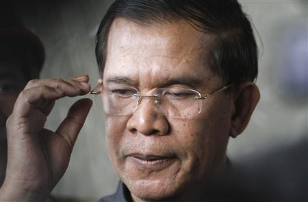 Cambodia's Prime Minister Hun Sen reacts as he speaks to the media during an inspection of a bridge construction site in Phnom Penh July 31, 2013. REUTERS/Samrang Pring