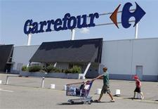 A customer pushes a shopping trolley as he leaves the Carrefour hypermarket in Brive-La-Gaillarde, central France, July 8, 2013. REUTERS/Regis Duvignau