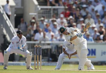 Australia's Michael Clarke (R) hits a ball from England's Graeme Swann as Matt Prior (L) looks on during the first day of the third Ashes test match at Old Trafford cricket ground in Manchester, northern England August 1, 2013. REUTERS/Phil Noble