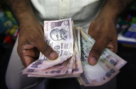A private money trader counts Rupee notes at a shop in Mumbai August 1, 2013. REUTERS/Vivek Prakash